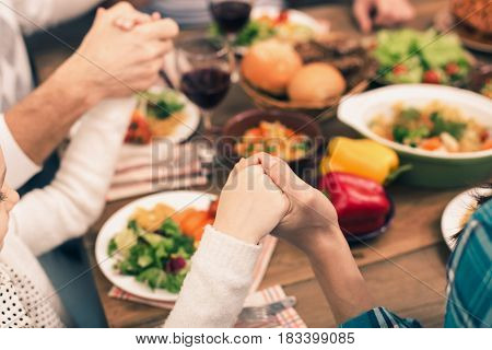 Family dinner. Beautiful family having meal. Tasty food on table. Happy family enjoying time together. They holding hands and praying