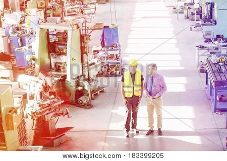 High angle view of male supervisor and manual worker having discussion in metal industry