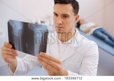 Joint dislocation. Serious intelligent male doctor holding an X ray photo and looking at it while seeing a joint dislocation