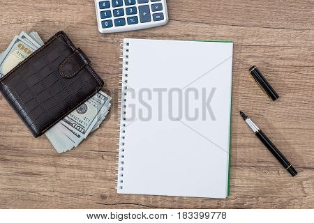 Notepad With Pen, Calculator, Dollar Bills On Desk.
