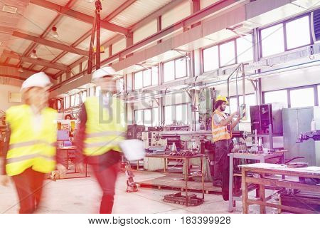 Blurred motion of business people with manual worker in background at industry