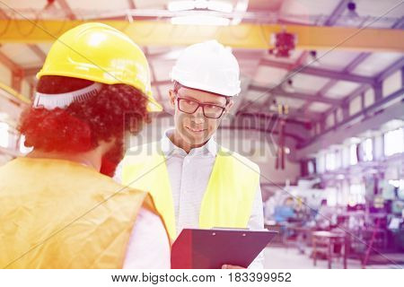 Male supervisor discussing with manual worker in metal industry