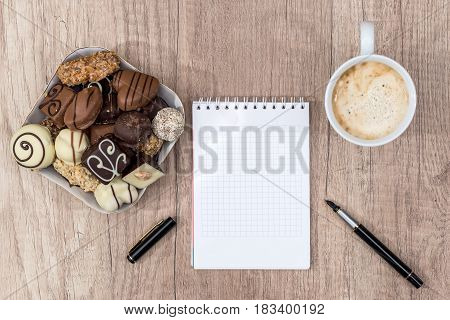 empty notepad with pen chocolate and cup of cappuccino.