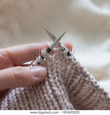 Lessons knitting by hand on needles and beige thread
