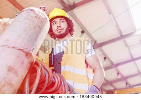 Low angle view of young manual worker moving gas cylinder in metal industry