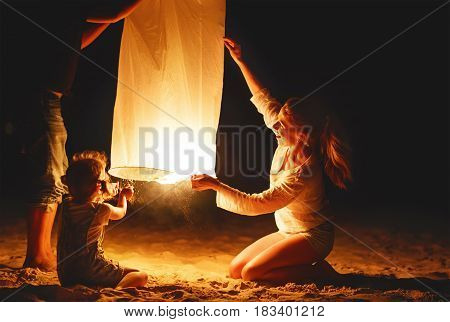 Family mother father daughter send air heavenly flashlight lamp in flight on beach