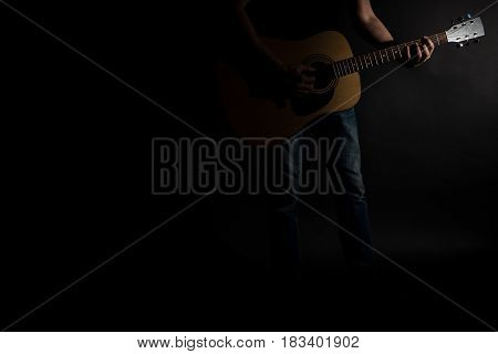 The guitarist in jeans plays an acoustic guitar on the right side of the frame on a black background