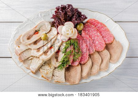 Meat plate with delicious pieces of sliced ham sausage olives beef tongue herbs and meat with radish on white plate and wooden table. Top view.