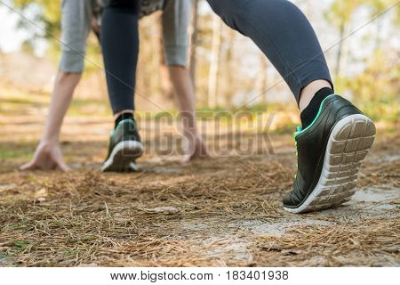 Girl In Sports Pants And Shoes, Stands At The Start Before Running, Leaning Hands, On The Nature.