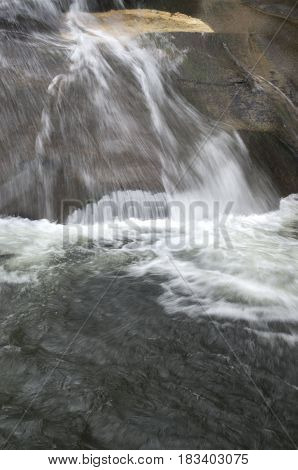 Water flows swiftly over rocks at Sliding Rock in the Pisgha National Forest