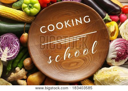 Cooking school concept. Wooden plate and fresh vegetables, closeup