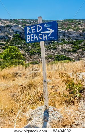 Wood sign showing the direction to a beach on hiking path