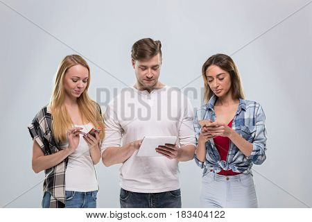 Casual People Group, Young Man Two Woman Happy Smile Using Cell Smart Phone Network Communication Over Grey Background