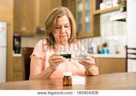 Elderly Woman Checking Her Medicines Expiration Date