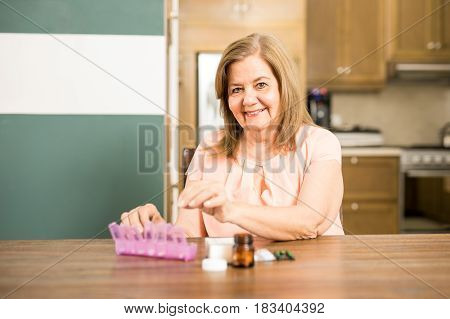 Happy Aged Woman Filling Her Pill Box