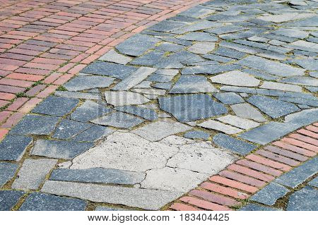 Road surface made of red bricks and granite tiles