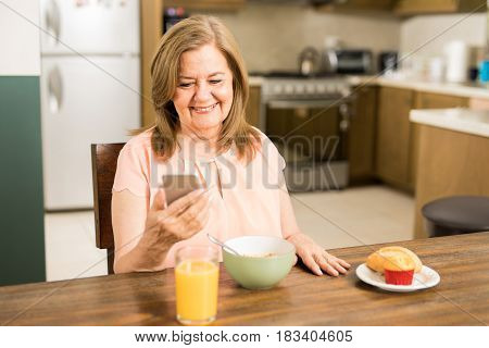 Happy Senior Woman Looking At Her Smartphone