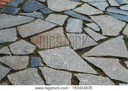 Road surface made of gray granite tiles