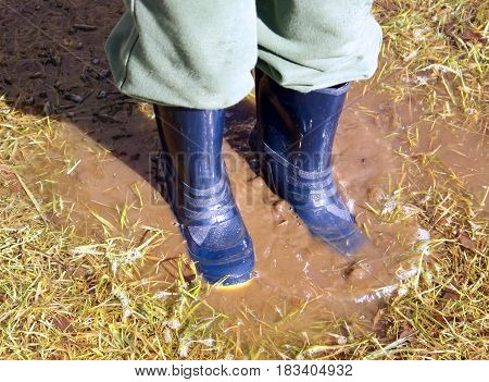 Closeup of boy in blue rain boots splashing in a muddy puddle in the grass after the rain sun shining