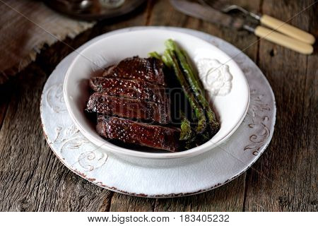 Duck breast baked in orange-honey sauce with asparagus. Rustic style.