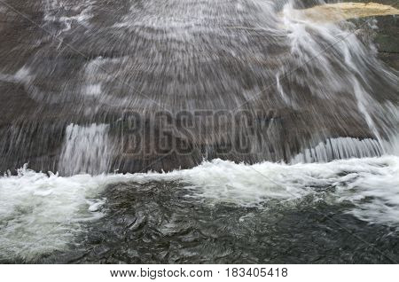 Water swiftly flows down sliding rock in the Pisgha National Forest in Western North Carolina