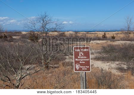 SANDY HOOK NEW JERSEY - February 24 2017: A National Park Service sign warns that the area behind is closed due to it being a wildlife mangement area. The Manhattan skyline is visable in the distance.