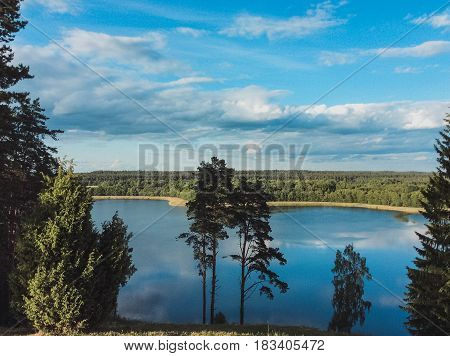 Picturesque view on the lake and forest at evening time just before the sunset.