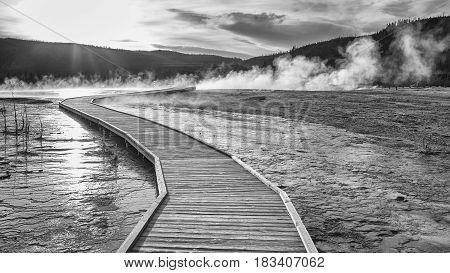 Wooden Bridge Over Steamy Terrain In Yellowstone At Sunset.