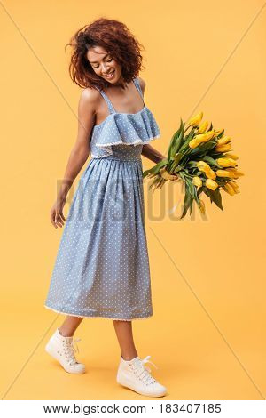 Vertical image of pleased african woman in blue dress holding bouquet of flowers over yellow background