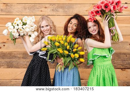 Three pleased women in dresses posing near the wooden wall and holding bouquets of flowers