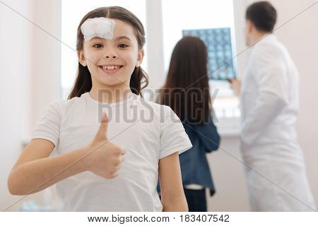 OK gesture. Delighted positive young girl smiling and looking at you while showing OK sign