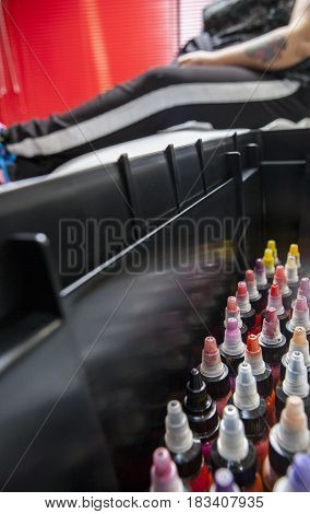 Bottles of colourful tattoo ink in a tattoo parlor with costumer waiting