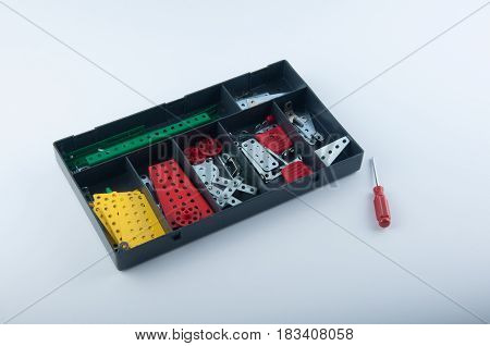 children's metal building kit in box and screwdriver lay on white background