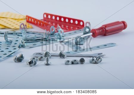 Silver bolts screw nuts screwdriver and red yellow metallic parts of kid's constructors lay on white background