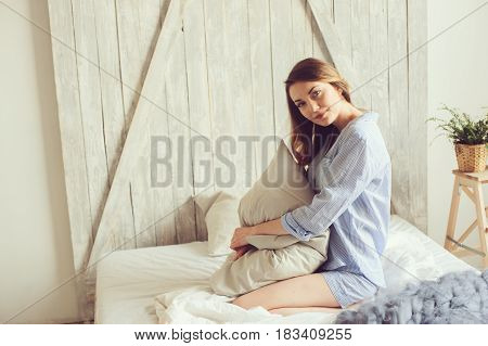 young woman in pajama wake up in the morning in cozy scandinavian bedroom and sitting on bed with white bedlinen. Casual lifestyle in modern interior
