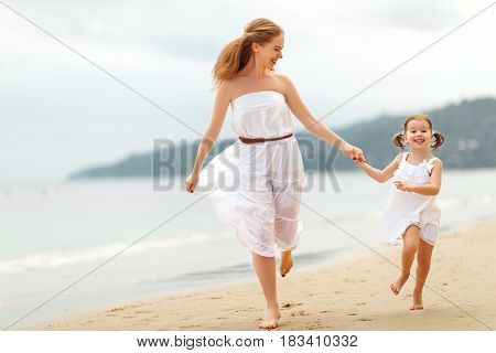 happy family mother and child daughter run laugh and play at beach