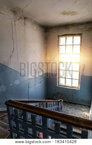 Big bright window and stairs in old dirty abandoned building in Voronezh, Russia. Urban exploration or Urbex concept.