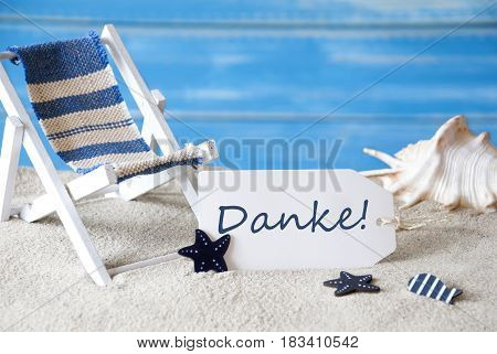 Summer Label With German Text Danke Menas Thank You. Blue Wooden Background. Card With Holiday Greetings. Beach Vacation Symbolized By Sand, Deck Chair And Shell.