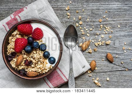 bowl of oat granola with yogurt fresh raspberries blueberries and nuts with a spoon on rustic wooden board for healthy breakfast. top view
