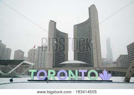 Toronto, Canada, circa february 2017: Nathan Phillips square in snowy winter and Toronto sign.
