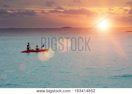 Canoe in the sea on a sunset