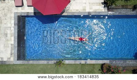 The young beautiful woman swims in the pool flat lay dron view.