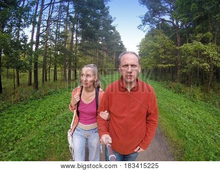 The man and the woman go on the way in the park the lens