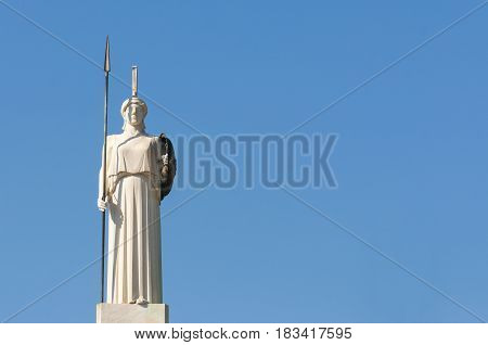 classical white Athena statue with blue sky behind