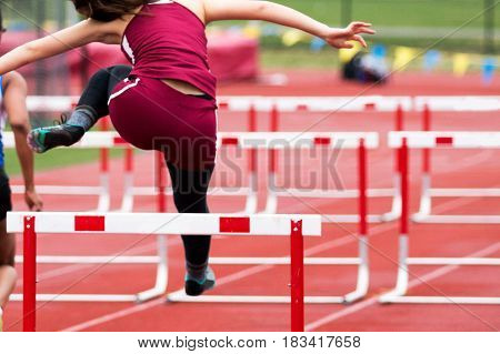 A high school girl racing over the hurdles during a track race.