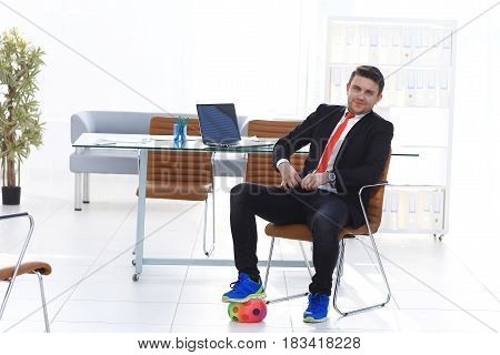 Business man playing football in his office