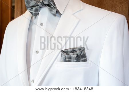 white tuxedo with silver gray plaid bow tie and handkerchief in pocket