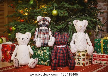 Teddy Bear Sitting Under Decorated With Lights Christmas Tree With Gift Boxes