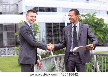 Two Businessmen Discussing Document Outside his Office