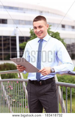 Young successful businessman with modern tablet outdoors